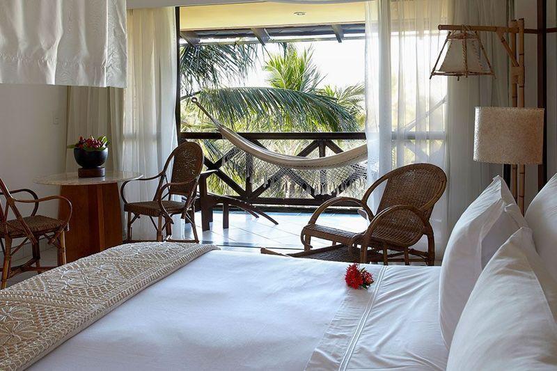 Detalhes da acomodação como cama de casal e varanda com rede
